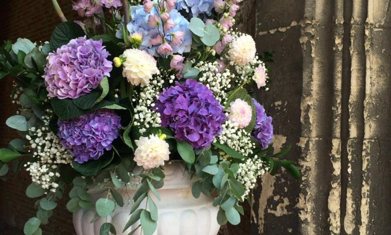 Blue and purple hydrangeas, delphinium, gypsophila and eucalyptus displayed in a white urn