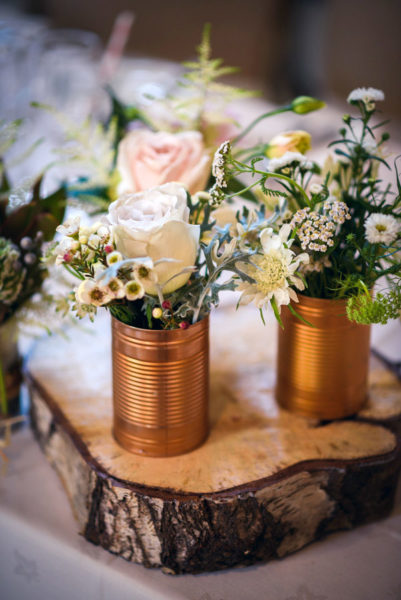 Wedding flowers displayed in copper tins