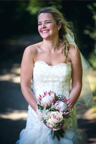 Bride holding a weddign bouquet with large tropical flowers