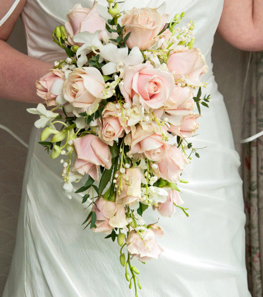 Bride holding a bouquet with white orchids with pale pink roses and lily of the valley