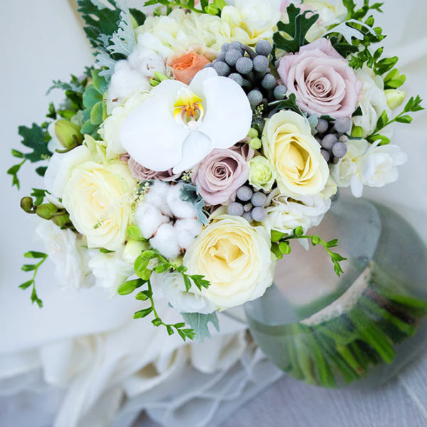 White and pastel colour weddgin flower arrangement with berries, roses and feature orchids