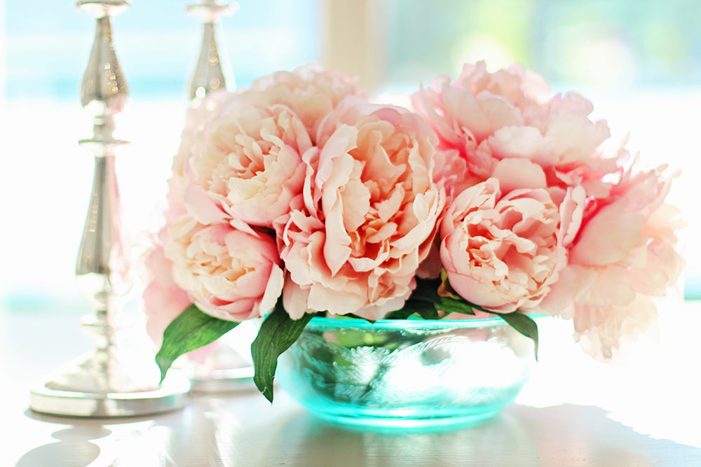 Peony flowers arranged in a flass bowl vase