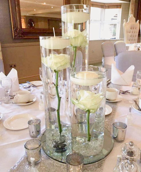 Three different height cylindrical vases each containing a single submerged rose and floating candle