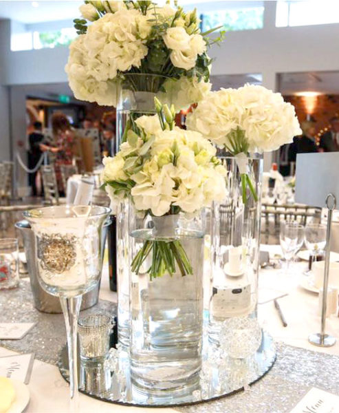 Wedding centrepice of three different height cyliner vases, each with hand-tied bouquet of cream flowers