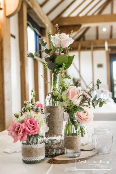 Jars and bottles of flowers displayed on a log slice
