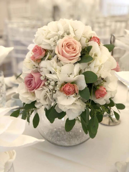 Cream and pink flower arrangement placed on top of a fish bowl vase