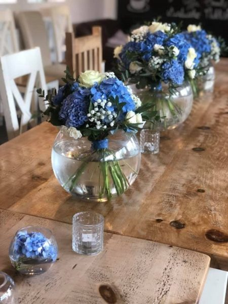 Deep blue flowers arranged as hand-toed bouquets placed in fish bowl vases
