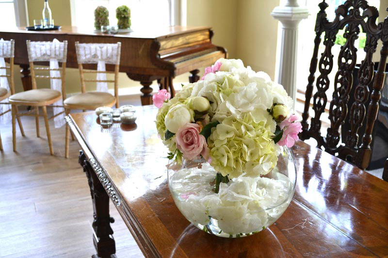 Hand-tied bouquet displayed in a fish bowl vase