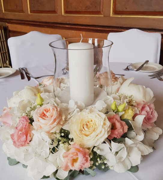 Glass hurricane vase with large candle surrounded by a ring of flowers