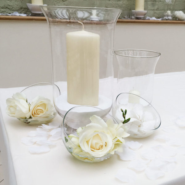 Hurricane lamp with large white candle inside, surroundd by three bowl vases with cream roses