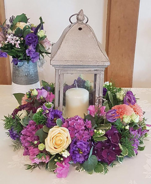 Rustic lantern centrepice surrounded by a ring of purple flowers