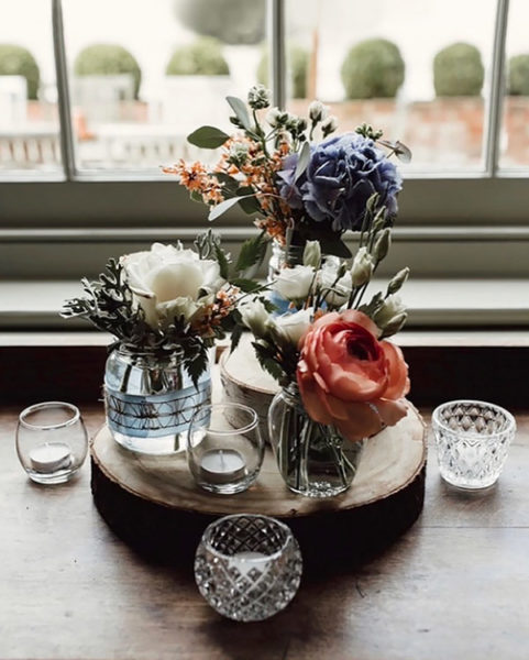 Jars of flowers displayed on a log slice