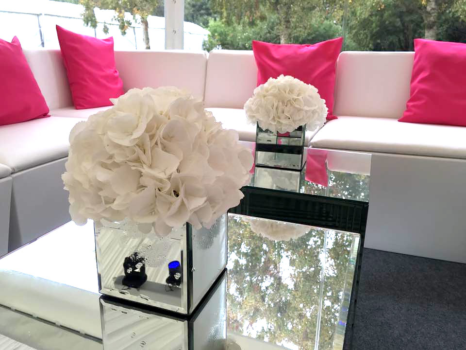 White flowers displayed in mirrored cube vases