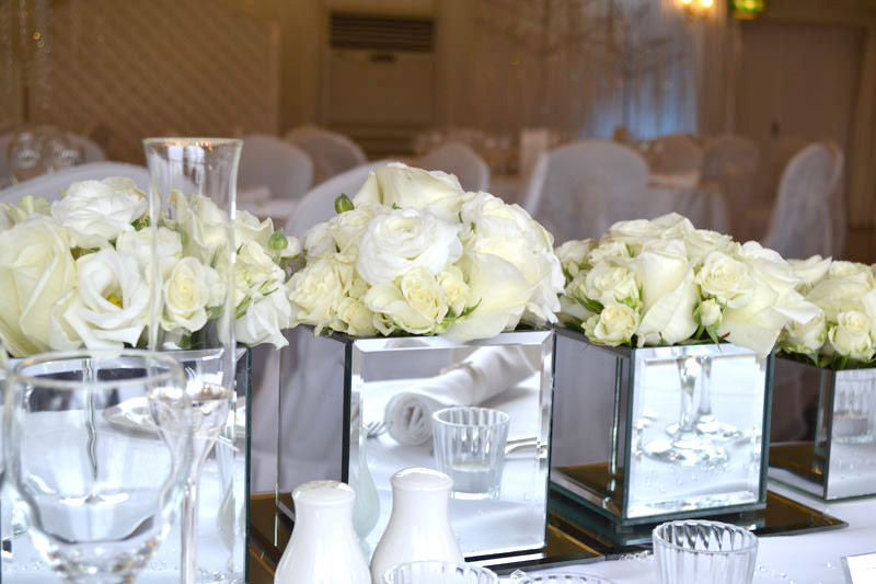 White roses displayed in mirrored cube vases