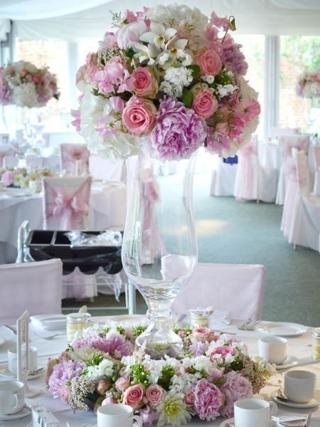 Tall glass vase with a pink and white flower arrangement on top and ring of flowers around the base